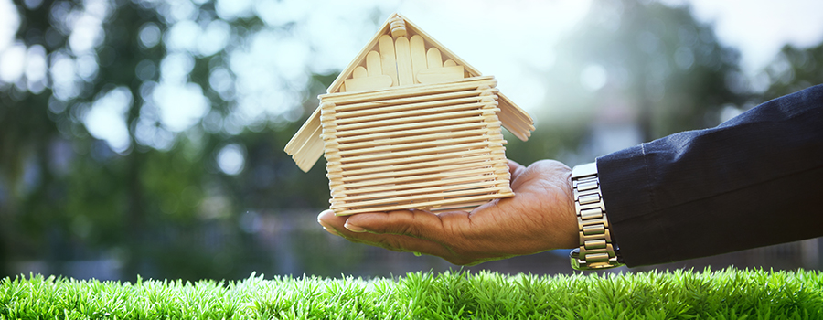 hand of business man and wood house model on beautiful green grass field use for housing ,residental real estate  and land development